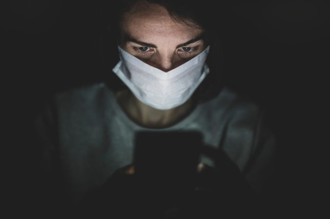 man-wearing-face-mask-using-his-phone-in-the-dark-4031909